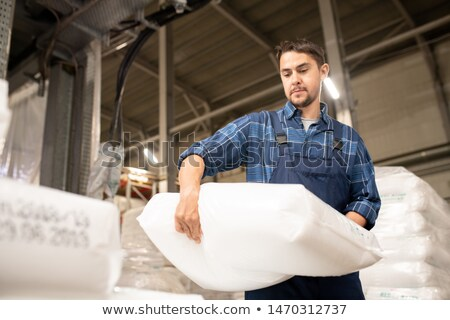 Young man in workwear carrying heavy white sack with polymer granules Stock photo © pressmaster