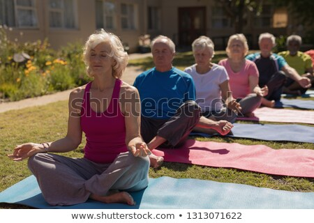 front view of group of active senior people performing yoga in the park they are sitting on yoga ma stock photo © wavebreak_media