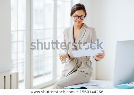 Pleased dark haired woman with smile, checks bills in documents, dressed beige business suit, drinks Stock photo © vkstudio
