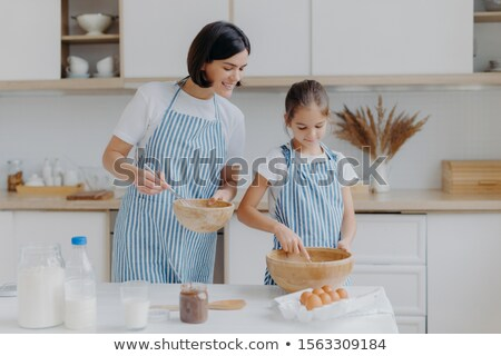 Preparing delicious meal and cooking together concept. Pleased mother looks attentively at how child Stock photo © vkstudio