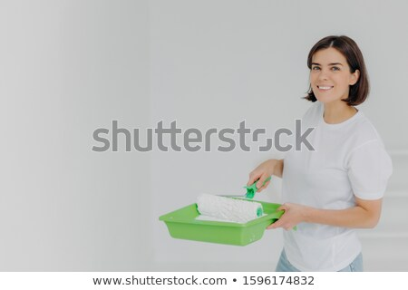 Happy lovely woman in white casual t shirt, poses with paint roller and special tray, makes refurbis Stock photo © vkstudio