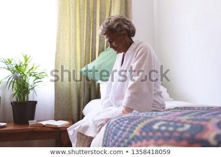 Side view of senior mixed race woman sitting upset in nursing home Stock photo © wavebreak_media