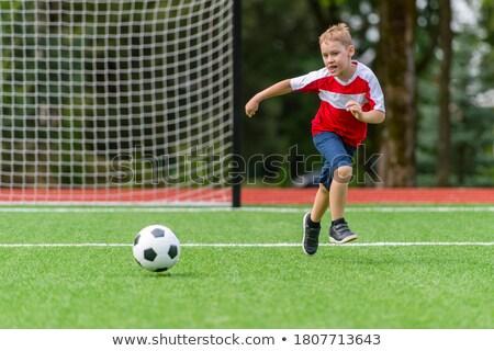kid kicking a ball about stock photo © stuartmiles