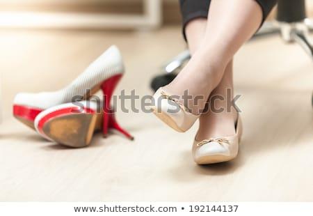Businesswoman wearing high heels shoes, sitting and massaging ti Stock photo © dacasdo