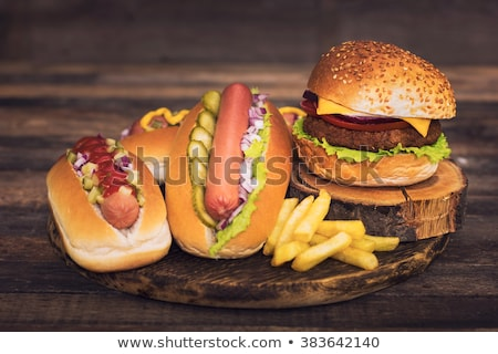 Fresh tasty hot dog with fried onions and fresh lettuce with mustard on a wooden tray Stock photo © mcherevan