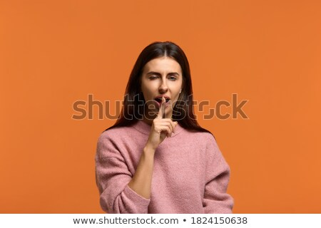 Happy playful young woman in hat standing and winking Stock photo © deandrobot