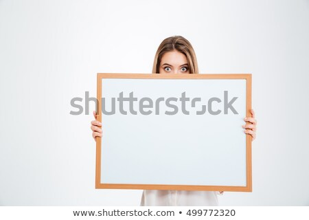 young woman with eyes wide open peeping from blank board stock photo © deandrobot