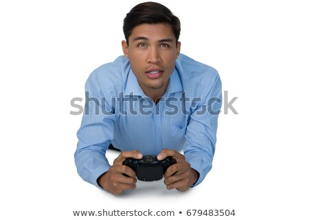 Stock photo: Young businessman lying down while playing video game