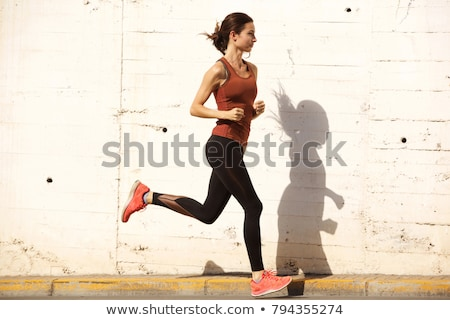 Full length portrait of a healthy motivated sportwoman stretching muscles Stock photo © deandrobot