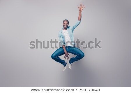 Full length portrait of an excited young afro american man Stock photo © deandrobot