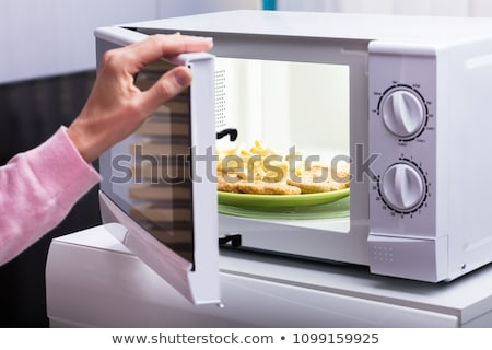 Stock photo: Woman Heating Fried Food In Microwave Oven