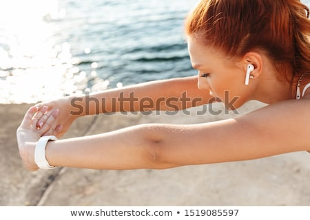 Beautiful young sports woman outdoors on the beach listening music with earphones make stretching ex Stock photo © deandrobot