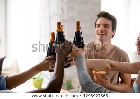 sonriendo · amigos · cerveza · botellas · bar - foto stock © andreypopov