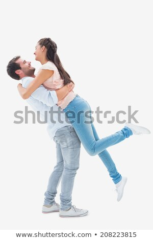 Young couple in love stand closely to each other, embrace and holds favourite dog, pose in empty roo Stock photo © vkstudio