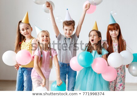 Happy birthday party. Joyful small children have fun together, raise arms and play with confetti, po Stock photo © vkstudio