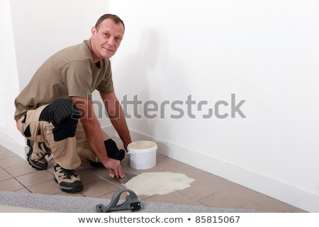 Carpet fitter spreading adhesive on a tiled floor Stock photo © photography33