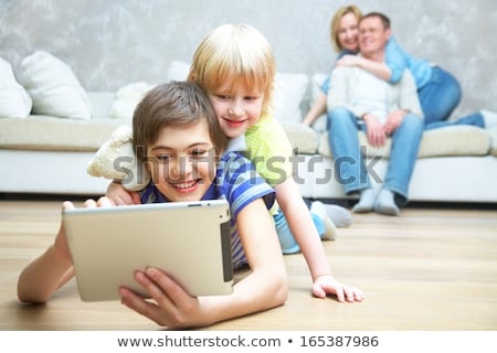 Happy siblings using laptop and tablet pc on sofa Stock photo © wavebreak_media