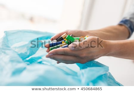 close up of hands putting batteries to rubbish bag Stock photo © dolgachov