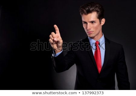 portrait of a young business man buttoning his suit stock photo © feedough