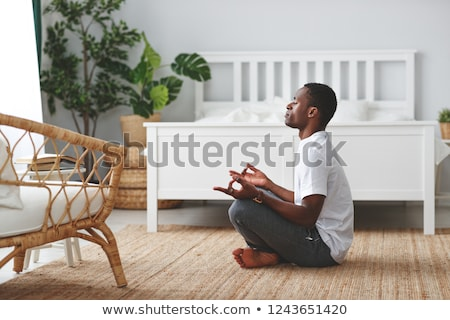 Man sitting on bed doing yoga stock photo © monkey_business