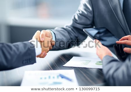 handshaking business person in office concept of teamwork and partnership double exposure with net stock photo © alphaspirit
