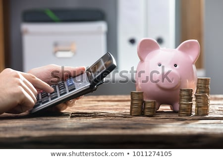 Stock photo: Piggy Bank And Stacked Coins On Wooden Desk