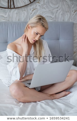 beatutiful woman in mens elegant white shirt sitting in bed with laptop stock photo © dash