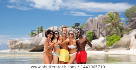 friends showing thumbs up over seychelles island  Stock photo © dolgachov
