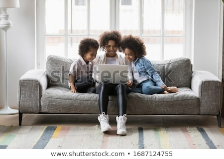 Three sisters girls sit on the sofa at home with laptop Stock photo © Lopolo