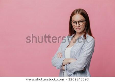 Sideways shot of prosperous businesswoman keeps arms folded, dressed in formalwear, wears spectacles Stock photo © vkstudio
