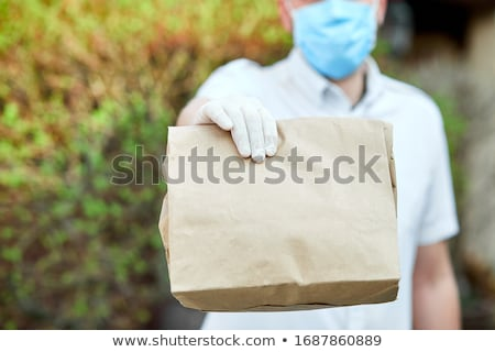 Courier, delivery man in medical latex gloves safely delivers online purchases a bouquet of flower Stock photo © Illia