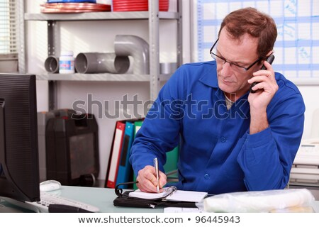 Plumber taking a call in an office and making an appointment in his diary Stock photo © photography33