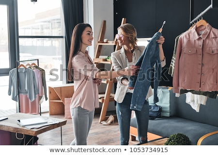Two happy women shopping in clothes store Stock photo © HASLOO