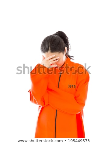 upset young asian woman with her head in hands in prisoners uniform stock photo © bmonteny