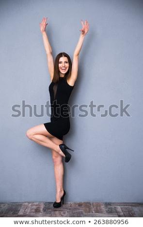 Young girl in black dress on gray background Stock photo © julenochek