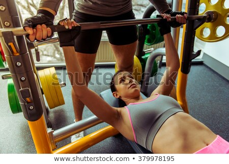 athletic woman lifting weights helped by trainer stock photo © wavebreak_media