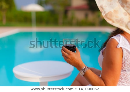 Woman having a drink by the pool Stock photo © IS2