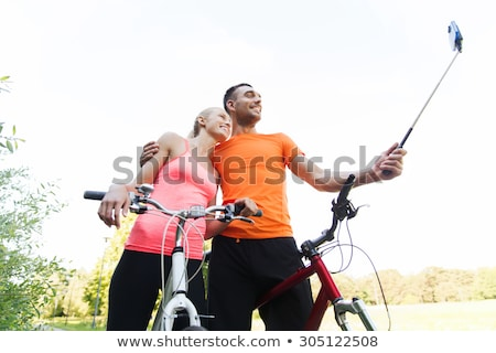couple with bicycle and smartphone selfie stick Stock photo © dolgachov