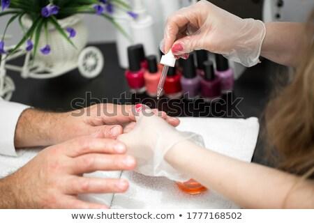 Beautician Applying Nail Oil On Man's Hand Stock photo © AndreyPopov