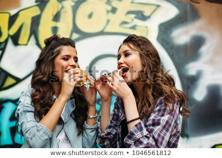 Couple of hipster girls eating burgers over graffiti. Stock photo © studiolucky
