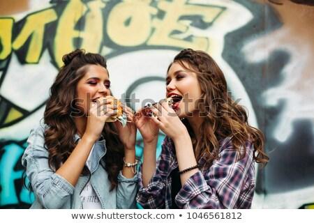 Couple of hipster girls eating burgers over graffiti. stock photo © studiolucky