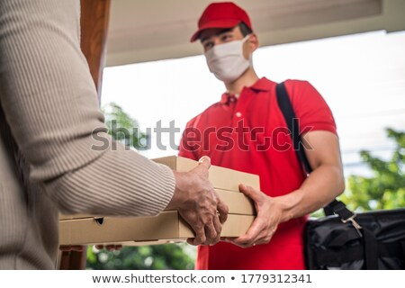 Female customer receiving the pizza order from delivery man Stock photo © Kzenon