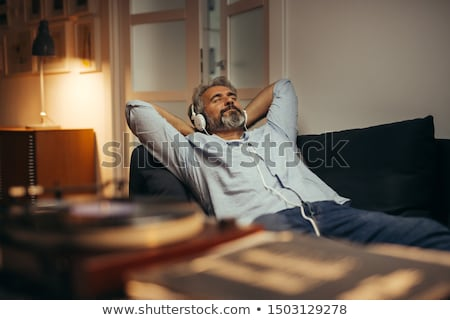 Relaxed man listening to music with earphones and eyes closed. Stock photo © lichtmeister