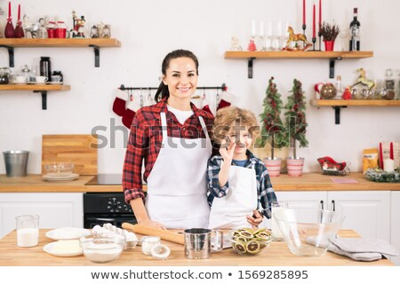 Happy young woman and her little son going to make cookies in the kitchen Stock photo © pressmaster