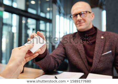 Bald mature businessman in eyeglasses and formalwear taking card from hotel room Stock photo © pressmaster