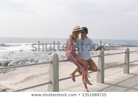 Side view of young Caucasian couple taking selfie while sitting at railing on a sunny day Stock photo © wavebreak_media