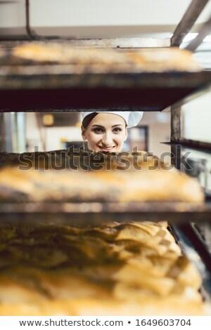 Gyönyörű pék nő néz kenyér fókusz Stock fotó © Kzenon