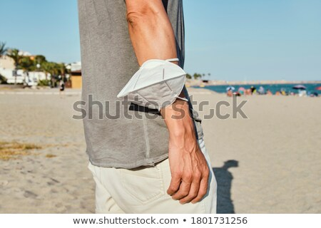 man with a face mask in his hand on the beach Stock photo © nito