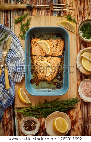 Roasted salmon in heat proof dish. With aromatic dill, lemon, salt and pepper on sides. Stock photo © dash