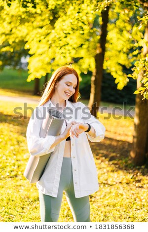 Happy laughing young woman standing on time clock stock photo © darrinhenry